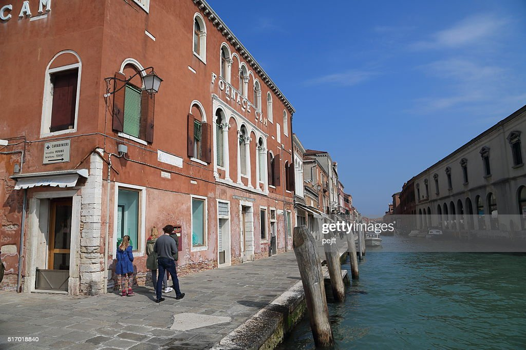 Canal, people and shops in Murano : Stock Photo