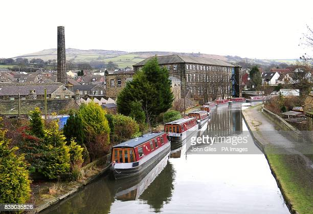 Canal pleasure boats moored for the winter on the Leeds and Liverpool canal alongside old mills at Silsden near Keighley West Yorkshire awaiting the...