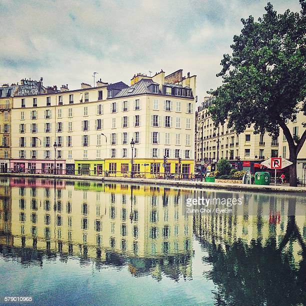 canal saint-martin against buildings in city - モバイル撮影 ストックフォトと画像