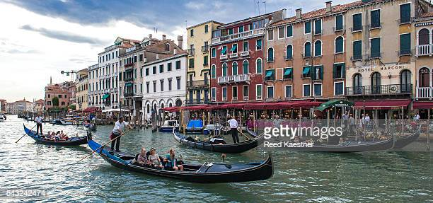 Canal scene of Venice Italy with tourists, gondolas and other boats.