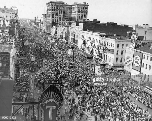 Canal Street view with crowds of people watching floats of the Mardi Gras parade pass buy New Orleans Louisiana 1950