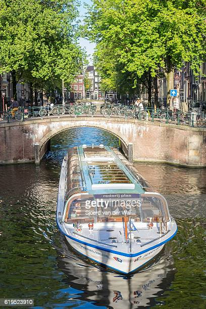 Canal tour boat at the Amsterdam Keizersgracht canal in Holland