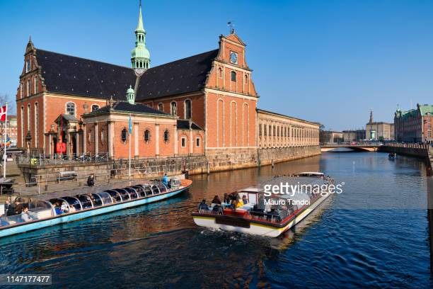 canal tours close holmens kirke church, copenhagen, denmark. - mauro tandoi stock photos and pictures