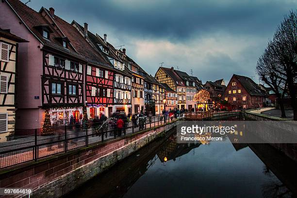 Canal waterfront view of traditional townhouses at dusk, Colmar, France