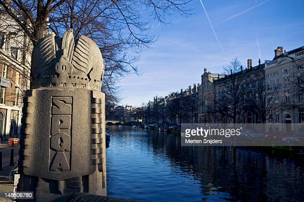 canal with carved letters spqa (senatus populusque amstelodamensis) on pillar in foreground. - merten snijders stock pictures, royalty-free photos & images