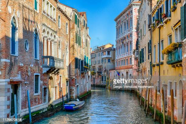 a canal with colorful houses in venice, italy - unesco stock-fotos und bilder
