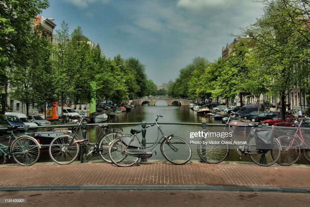 Canal with private boats on both sides and bicycles tied to the bridges in Amsterdam, Netherlands : Foto de stock