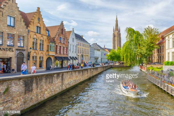 canals, traditional buildings and tower of church of our lady in brugge, belgium - bruges stock pictures, royalty-free photos & images