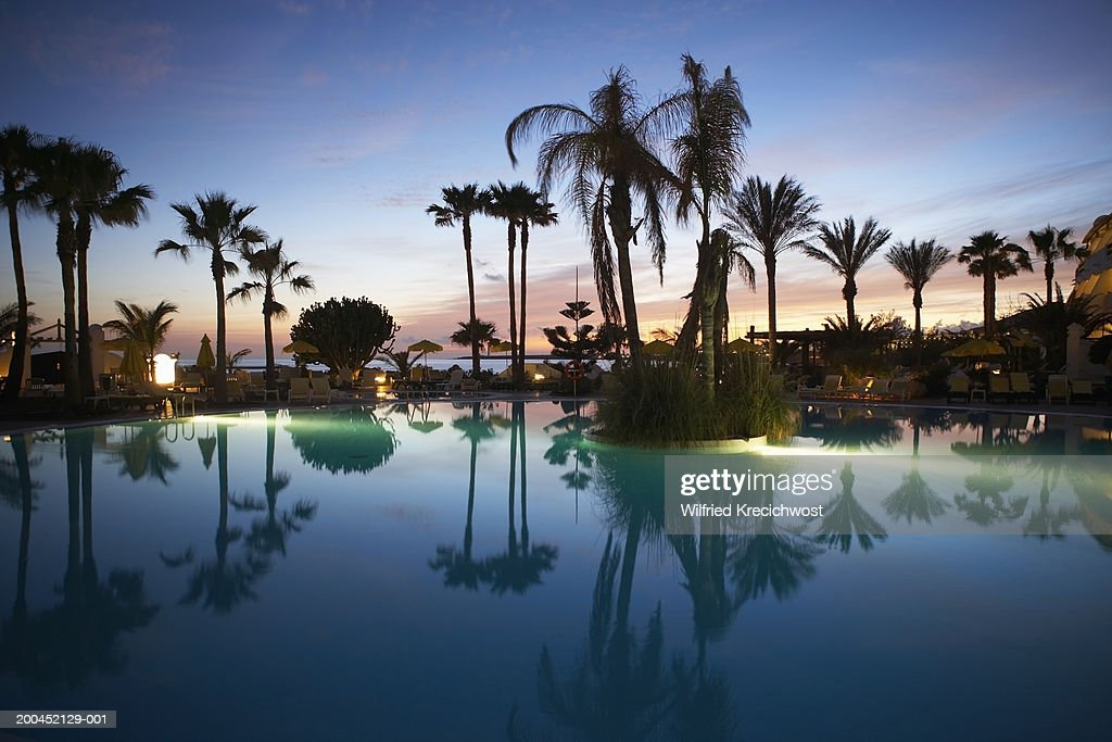 Canary Islands, Lanzarote, swimming pool and palm trees, sunset : Stock Photo