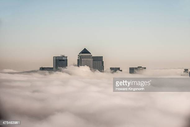 canary wharf above the clouds - clear sky stock pictures, royalty-free photos & images