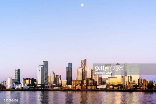 canary wharf and the city skyline of london docklands - waterfront stock pictures, royalty-free photos & images