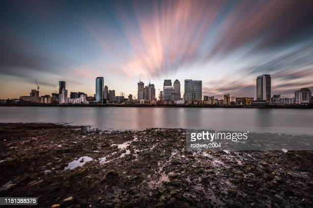 canary wharf from across the river at dusk - isle of dogs london stock pictures, royalty-free photos & images