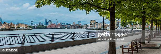 canary wharf, the thames riverbank, on the background the thames river and the town - water's edge stock pictures, royalty-free photos & images