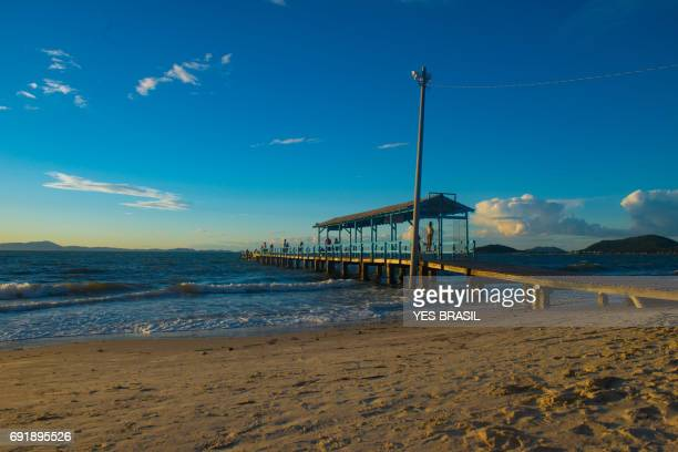 canasvieiras beach in florianópolis, santa catarina, brazil - fishermen at the pier - orange grove stock photos and pictures