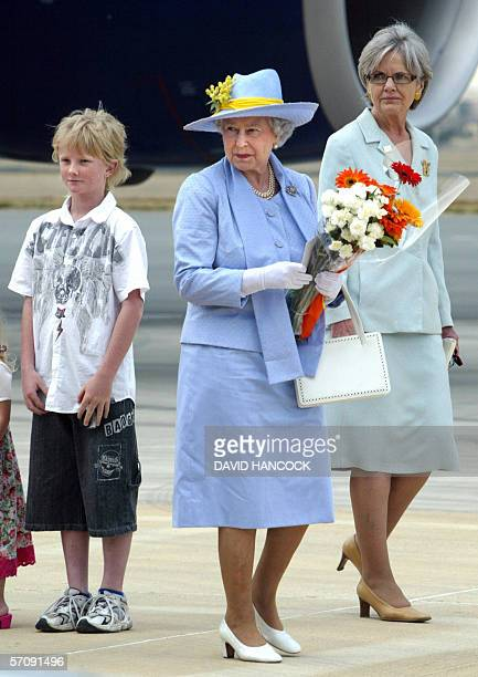 Queen Elizabeth II prepares to board her plane for the flight to Melbourne after receiving farewell flowers from local children in Canberra 15 March...