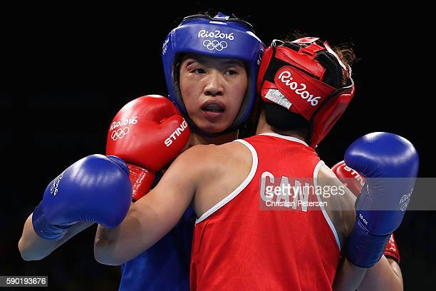 Cancan Ren of China is tied up with Mandy Bujold of Canada in the boxing Women's Fly Quarterfinal 2 on Day 11 of the Rio 2016 Olympic Games at...