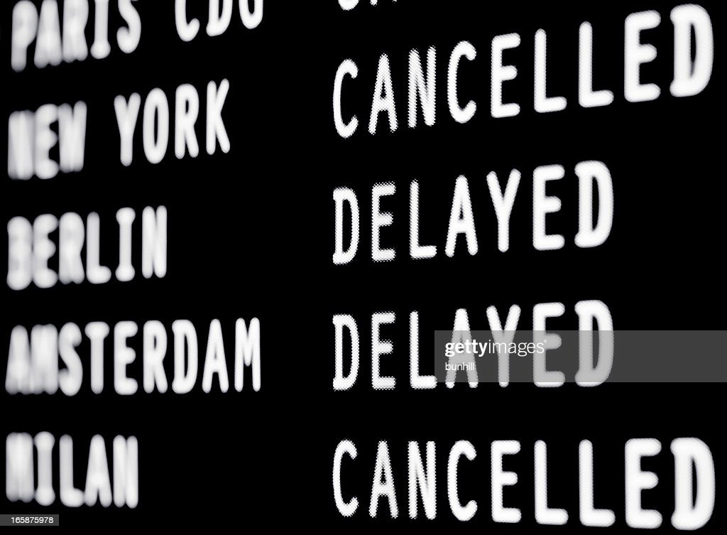 Cancelled and delayed flights on a airport screen : Stock Photo
