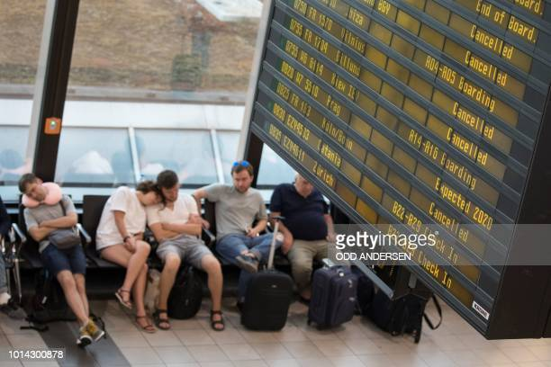 Cancelled Ryanair flights are seen on the announcement board as passengers catch up on sleep in the terminal at Schoenefeld Airport in Berlin on...
