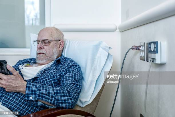 cancer chemotherapy patient reading smart phone - chemotherapy stock pictures, royalty-free photos & images