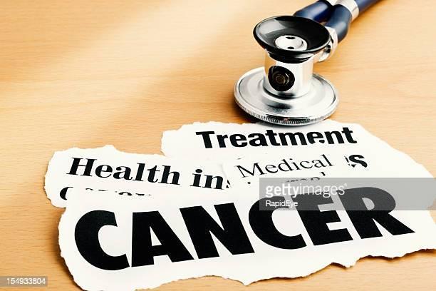 Cancer headlines alongside stethoscope on desk