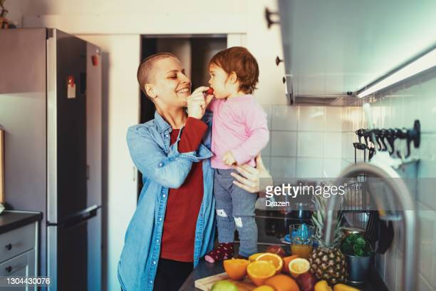cancer mother making breakfast with daughter - cancer illness stock pictures, royalty-free photos & images