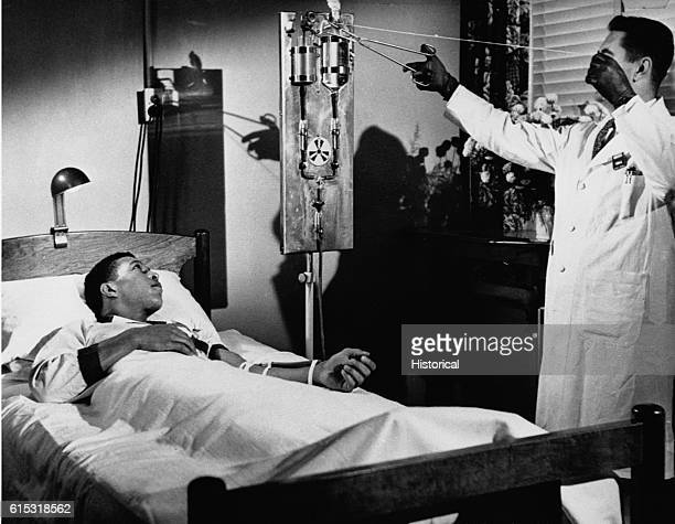 A cancer patient looks on as a physician pours gallium into a flask on the intravenous stand at Oak Ridge Cancer Research Hospital Ca 19471972 Oak...