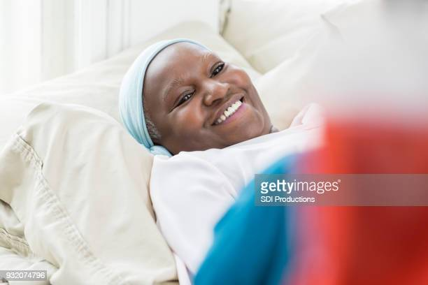 cancer patient smiles at healthcare professional - hospice stock pictures, royalty-free photos & images