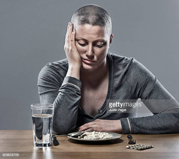 Cancer Patient Staring at Plate Full of Pills