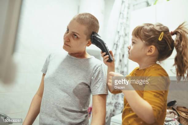 cancerpatient kvinna i badrummet rakning eller trimning hennes hår med sin dotter - människokroppsdel bildbanksfoton och bilder