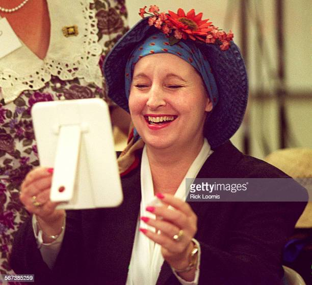 LScancer#20430RL–KODAK C–Fountain Valley–Candy Friesner of Anaheim laughs at her new look while modeling a variety of ways to wear hats and scarfs to...