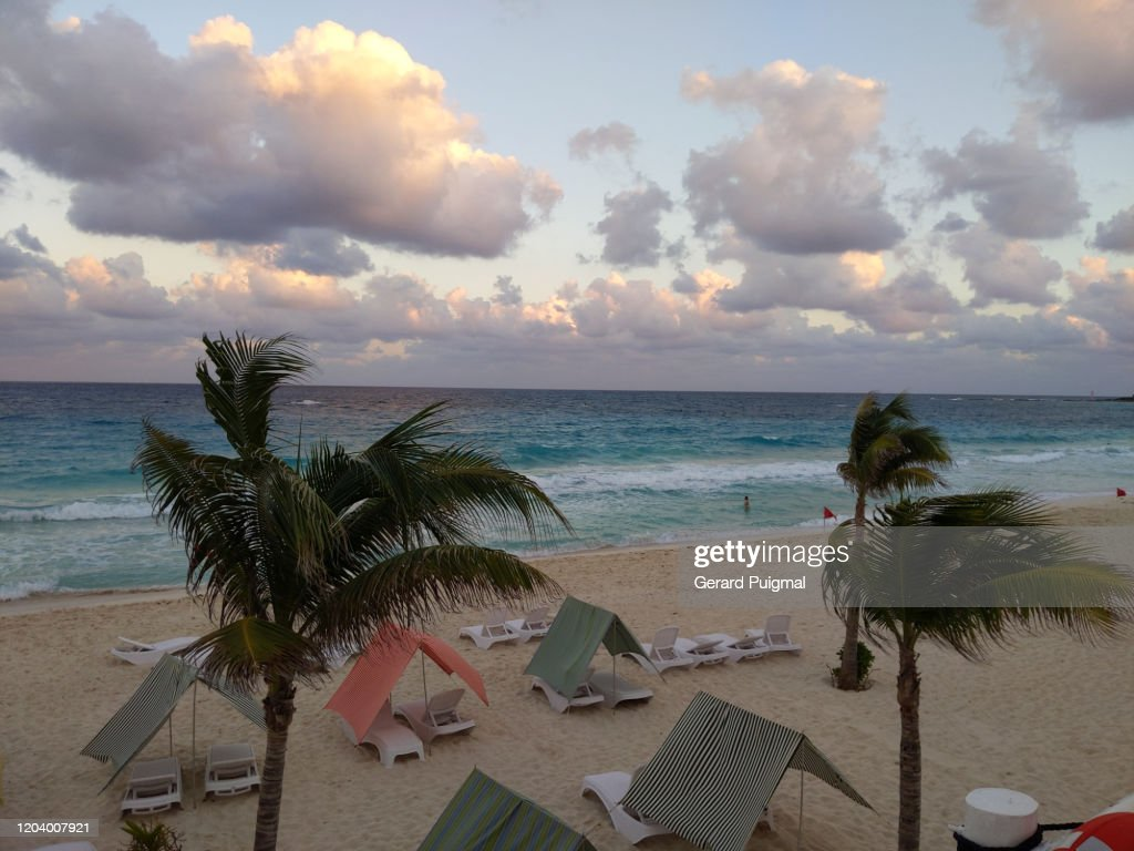 Cancun Beach During The Sunset There Are Palm Trees And Colorful Tents On The Sand High Res Stock Photo Getty Images