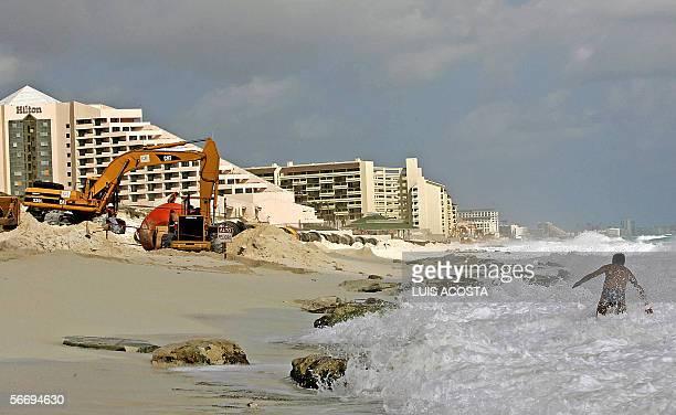 Un turista intenta banarse en una playa de Cancun Mexico el 28 de enero de 2006 cerca de un area donde trabajan en la recuperacion de la zona Las...