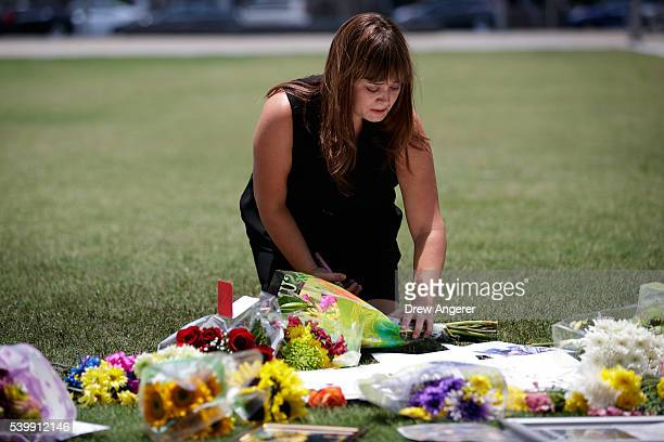 Candace Crispo a friend of Shane Tomlinson who died in the shooting at Pulse Nightclub lays flowers at a makeshift memorial at Dr Phillips Center for...