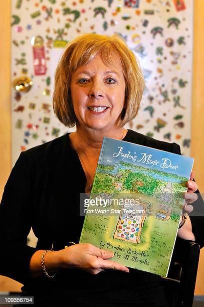 "Candace Schneller holds a copy of her children's book ""Jayden's Magic Door"" while standing in front of its inspiration on February 16 in Fort Worth,..."