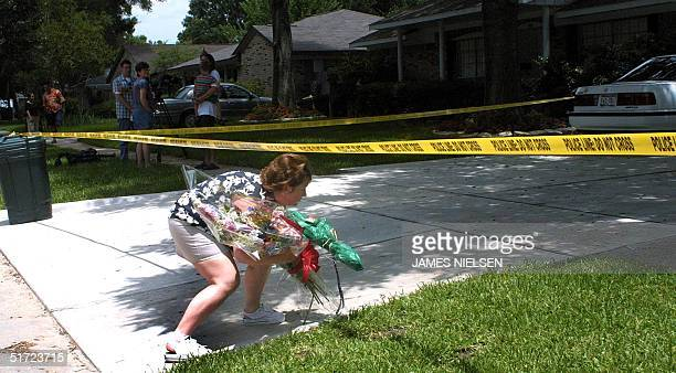 Candace Watson ducks under police tape to put flowers on a makeshift shrine of flowers and stuffed animals in front of the home of Andrea Pia Yates...