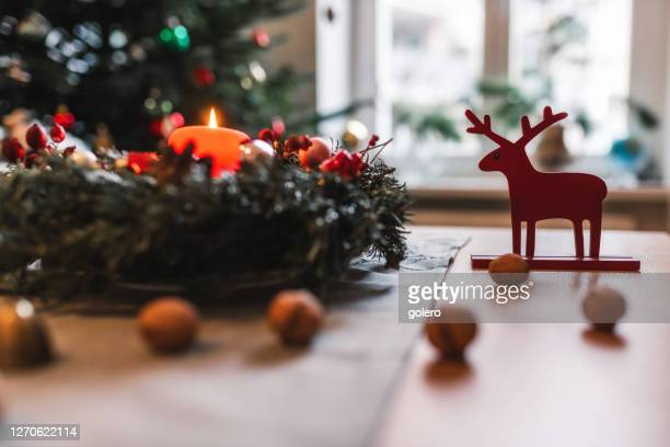 candel di corona d'avvento che brucia davanti all'albero di natale festivo - avvento foto e immagini stock