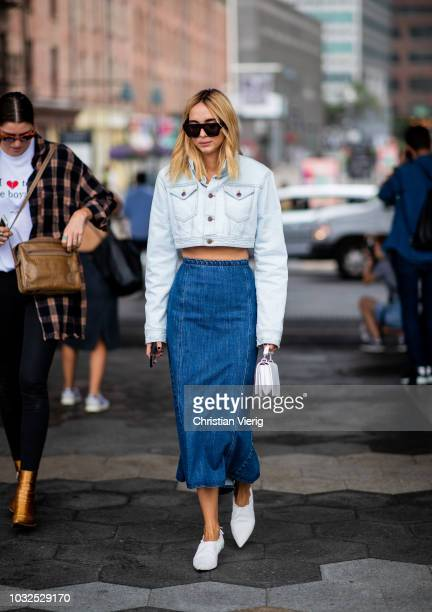 Candela Novembre wearing light cropped denim jacket denim midi skirt white shoes seen outside Michael Kors during New York Fashion Week Spring/Summer...