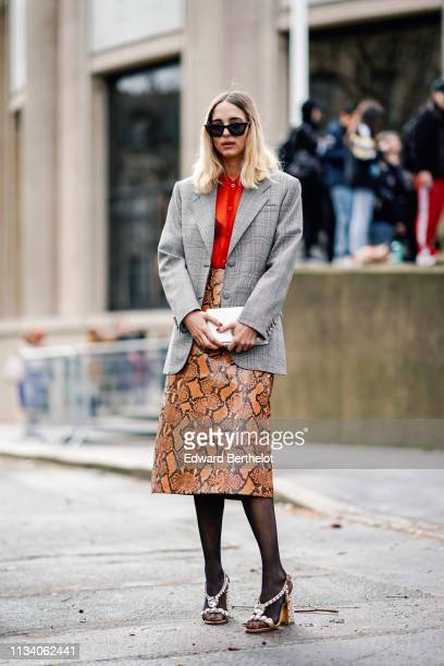 Candela Novembre wears a gray blazer jacket a red shirt a necklace a brown snake print leather skirt shoes outside Miu Miu during Paris Fashion Week...