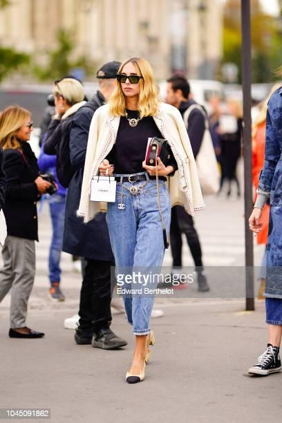 Candela Novembre wears a white jacket a necklace a black top blue jeans Chanel slingback shoes outside Chanel during Paris Fashion Week Womenswear...