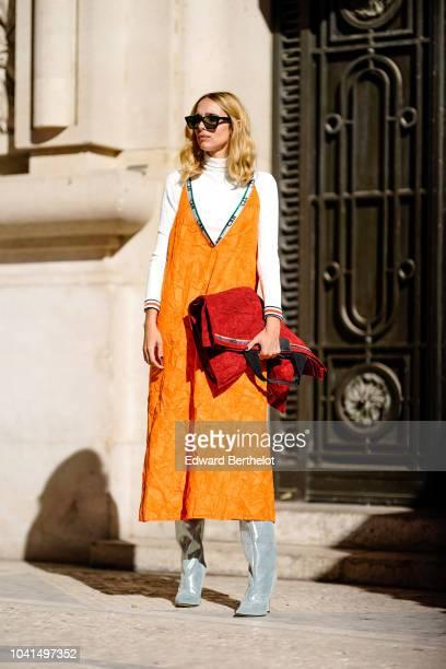 Candela Novembre wears an orange low neck dress over a white turtleneck top glitter gray boots outside Margiela during Paris Fashion Week Womenswear...