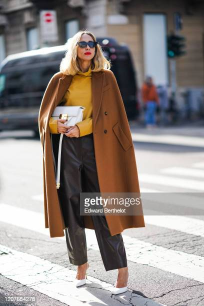 Candela Novembre wears an orange pullover a white bag a brown long coat black leather pants white pointy shoes outside Max Mara during Milan Fashion...