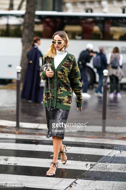 Candela Novembre wears earrings yellow sunglasses a white turtleneck a green camouflage cardigan a grey camouflage bag a shiny black crocodile...
