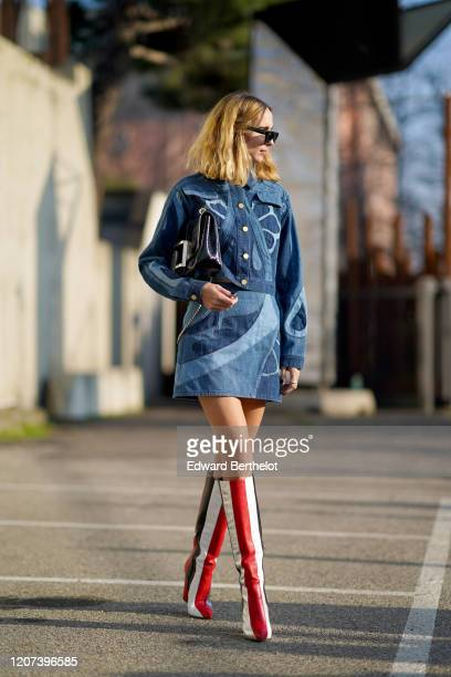 Candela Novembre wears sunglasses a blue denim dress with printed patterns a black bag red white and black striped high boots outside Alberta...