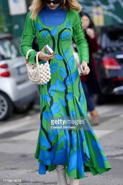 Candela Novembre wears sunglasses, a blue turtleneck pullover, a blue and green floral print dress, a white beaded bag made of large pearls, white...