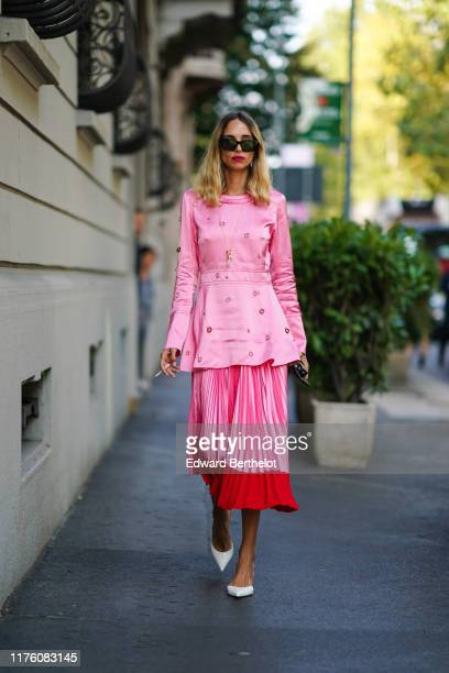 Candela Novembre wears sunglasses a pink lustrous dress with attached rings and shoulder pads a pink and red pleated skirt white shoes outside the...