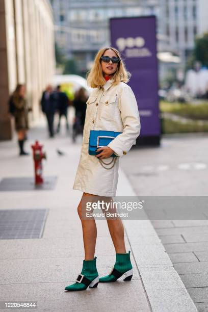 candela Novembre wears sunglasses a white jacket dress a blue bejeweled bag green pointy shoes outside Vivetta during Milan Fashion Week Fall/Winter...