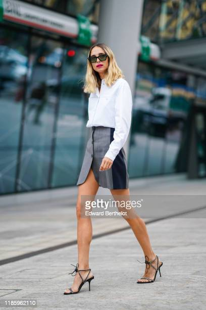 Candela Novembre wears sunglasses a white shirt a gray skirt high heeled shoes outside the Sportmax show during Milan Fashion Week Spring/Summer 2020...