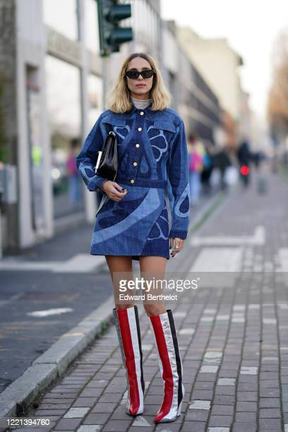 Candela Novembre wears sunglasses, a white turtleneck top, a black bag, a blue denim short dress with buttons, red and white leather striped boots,...