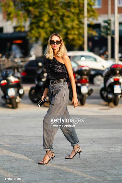 Candela Novembre wears sunglasses, earrings, a black top with mesh, lace and tweed, gray denim pants, a leather and metallic belt, outside the...