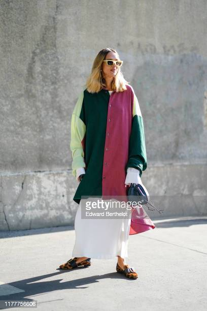 Candela Novembre wears yellow sunglasses, a colorfully patched long tunic, a flowing white long skirt, a blue bag, leopard pattern moccasins, outside...
